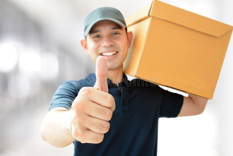 Lieferbote, der einen Kasten, Daumen aufgebend trägt lizenzfreies stockfoto