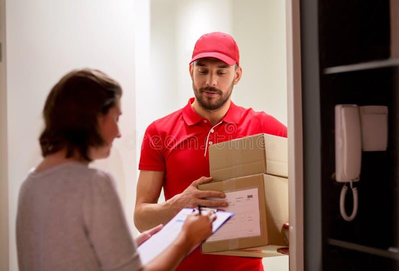 Lieferbote und Kunde mit Paketkästen zu Hause lizenzfreies stockbild