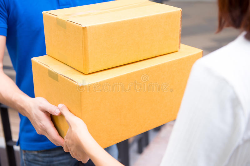 Lieferer in der blauen Uniform Paketkästen übergebend einer Frau lizenzfreie stockfotos