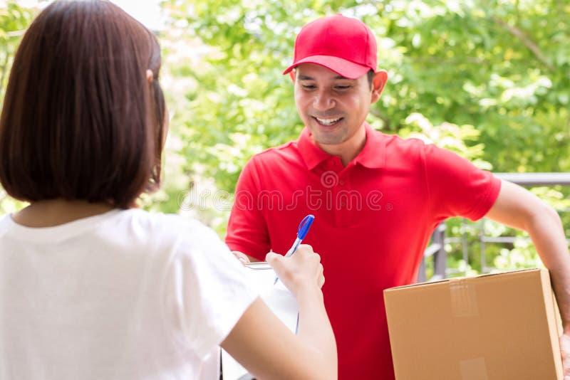 Lieferer, der Paket an eine Frau liefert lizenzfreies stockfoto