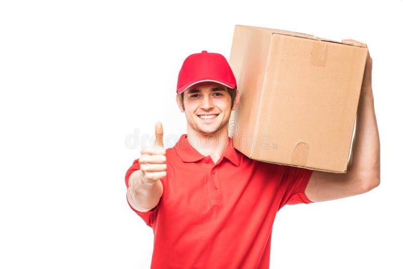 Lieferer, der sich Daumen und die lächelnden stehenden nahen Pappschachteln lokalisiert auf weißem Hintergrund zeigt lizenzfreie stockfotografie