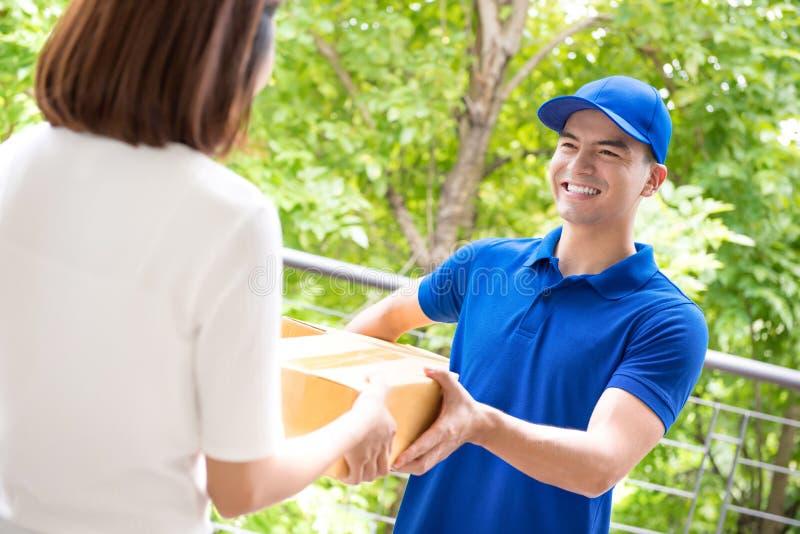 Lieferer im blauen einheitlichen liefernden Paketkasten zu einer Frau stockfoto