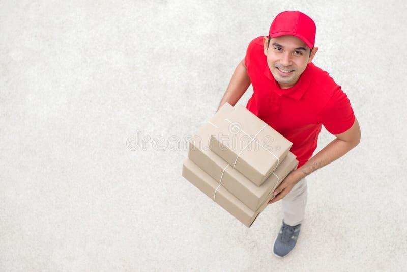 Lieferer im roten einheitlichen haltenen Kasten stockfotografie