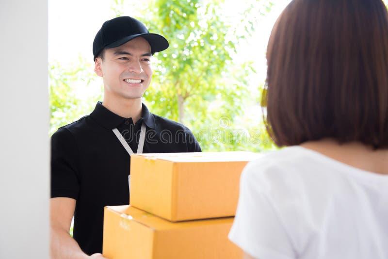 Lieferer liefern Pakete an eine Frau stockfotografie