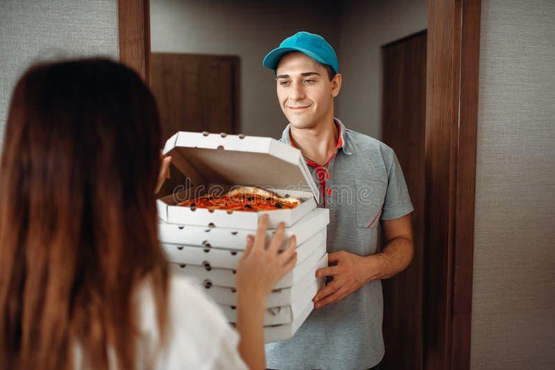 Lieferer zeigt dem Kunden Pizza an der Tür stockfoto