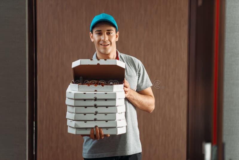 Lieferer zeigt die frische Pizza und liefert Service stockfotografie