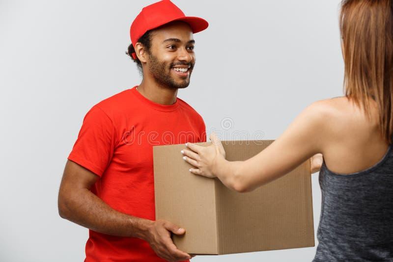 Lieferungs-Konzept - hübscher Afroamerikanerlieferer, der dem Hausbesitzer Paket gibt Lokalisiert auf grauem studi lizenzfreie stockfotos