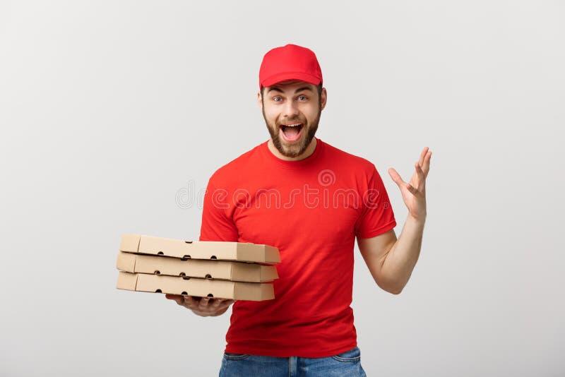 Lieferungs-Konzept: Hübscher Pizzabotekurier in der roten Uniform mit der Kappe, die Pizzakästen hält Lokalisiert auf Weiß lizenzfreies stockbild