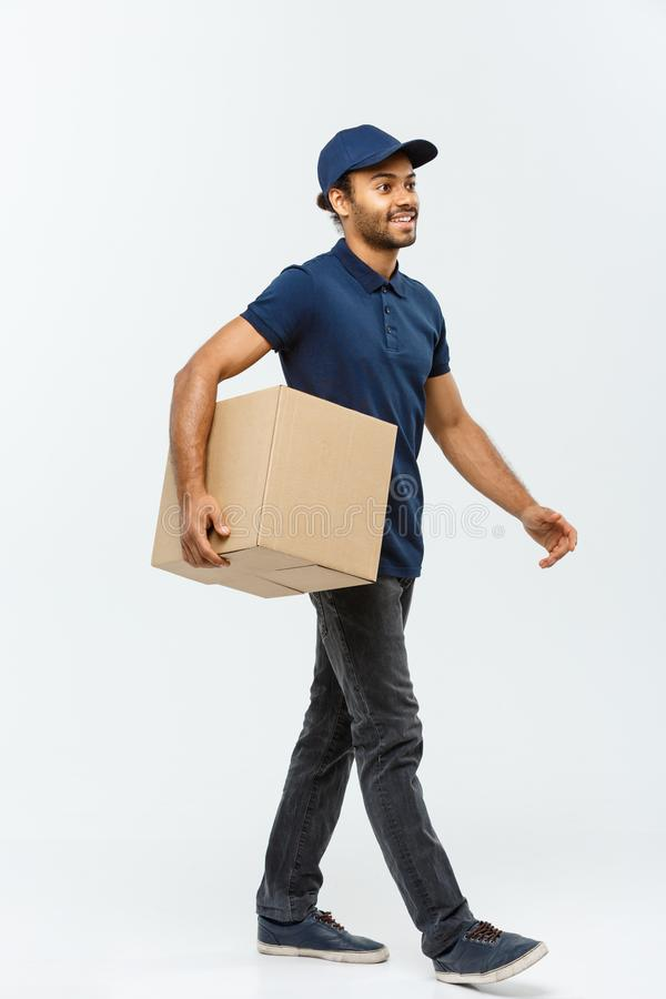 Lieferungs-Konzept - Porträt des glücklichen Afroamerikanerlieferers im blauen Stoff gehend ein Kastenpaket zu schicken lizenzfreie stockfotos