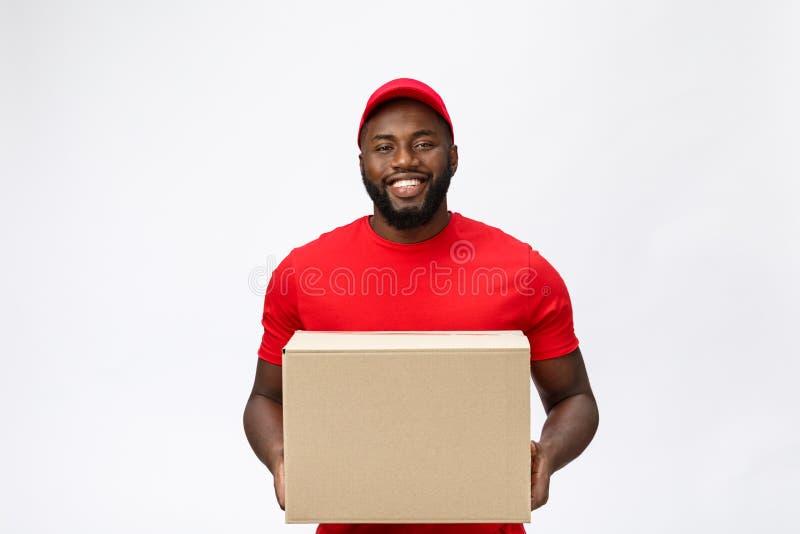 Lieferungs-Konzept - Porträt des glücklichen Afroamerikanerlieferers im roten Stoff, der ein Kastenpaket hält Getrennt auf Grau lizenzfreies stockbild