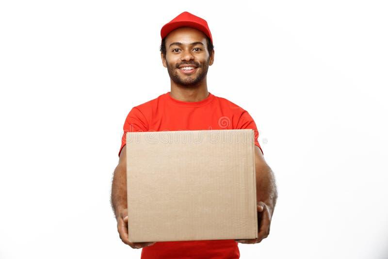 Lieferungs-Konzept - Porträt des glücklichen Afroamerikanerlieferers im roten Stoff, der ein Kastenpaket hält Lokalisiert auf Wei lizenzfreie stockfotografie
