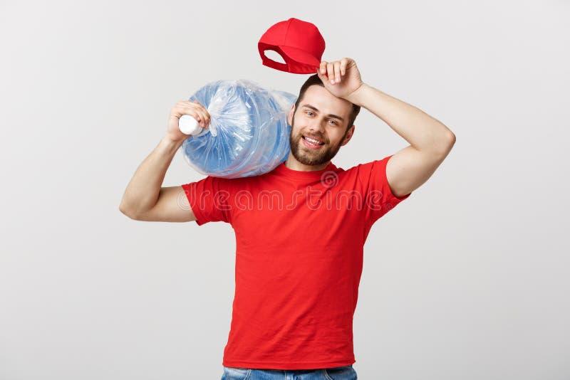 Lieferungs-Konzept: Porträt des lächelnden Tafelwasserlieferungskuriers in rotem T-Shirt und der Kappe tragendem Behälter des neu lizenzfreie stockfotografie