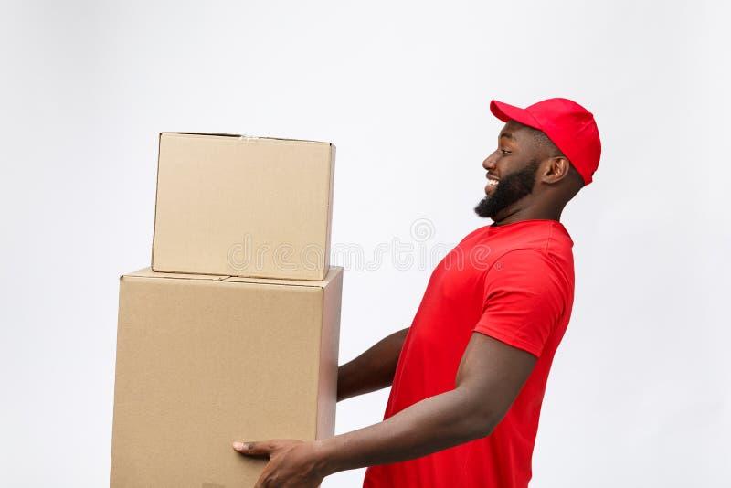 Lieferungs-Konzept - Seitenansicht Porträt des glücklichen Afroamerikanerlieferers im roten Stoff, der ein Kastenpaket hält stockbild
