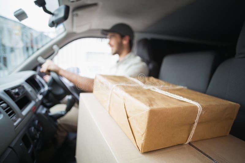 Lieferungsfahrer, der Packwagen mit Paketen auf Sitz fährt lizenzfreie stockbilder