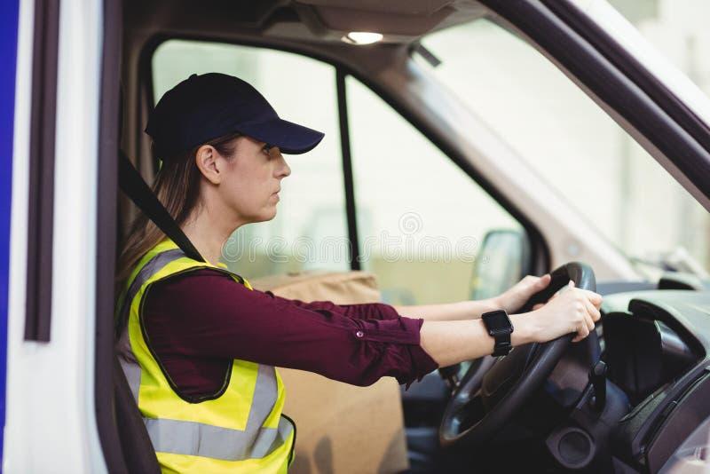 Lieferungsfahrer, der Packwagen mit Paketen auf Sitz fährt lizenzfreie stockfotos