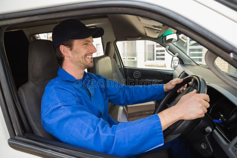 Lieferungsfahrer, der in seinem Packwagen lächelt lizenzfreie stockfotos