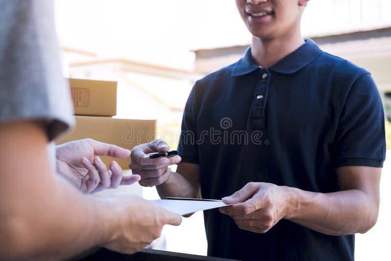 Lieferungspostmann, der Paketkasten zur Empfänger- und Unterzeichnungsform, unterzeichnende Ablieferungsbescheinigung des jungen  lizenzfreies stockfoto