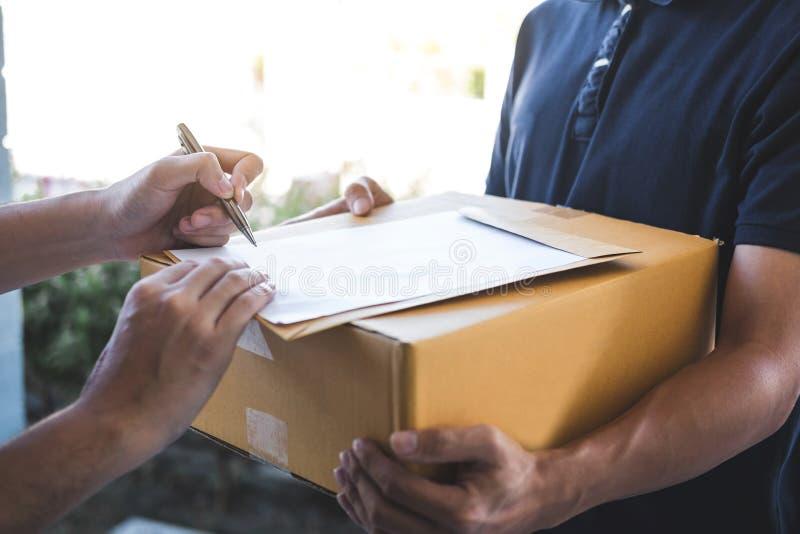Lieferungspostmann, der Paketkasten zur Empfänger- und Unterzeichnungsform, unterzeichnende Ablieferungsbescheinigung des jungen  stockfotos