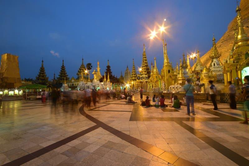Liefhebbers die & zich bij Overvolle Shwedagon-Pagode in de avond tijdens zonsondergang bevinden zitten royalty-vrije stock afbeelding