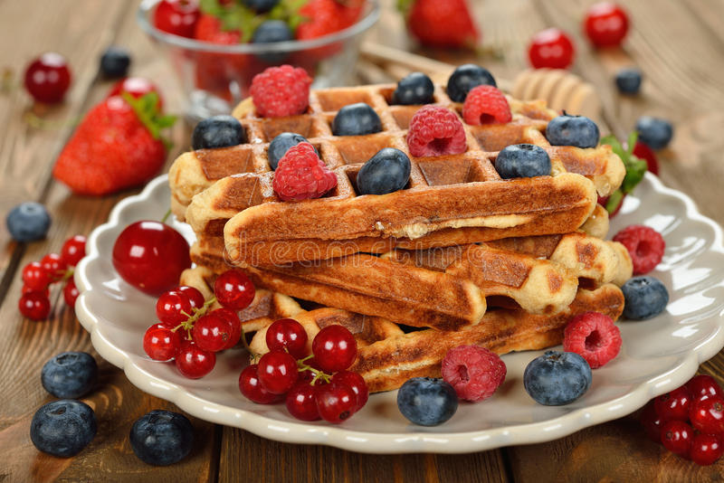 Liege waffles with berries. On brown background stock photos