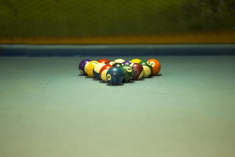Liegen mehrfarbige Billardkugeln auf dem blauen Stoff der Tabelle in der Pyramide eines Dreiecks lizenzfreie stockfotografie