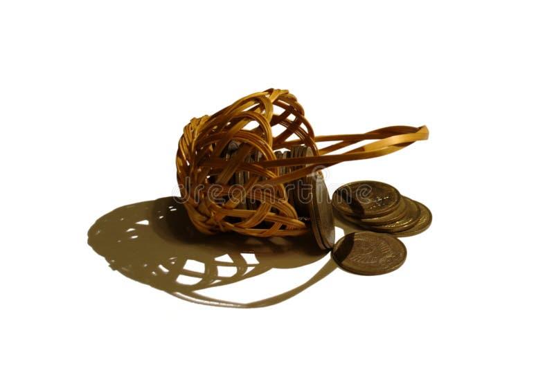 Liegender Weidenkorb mit zerstreuten Münzen stockbild