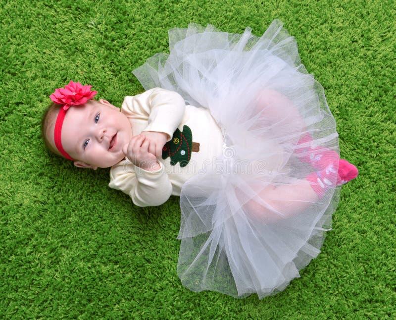 Liegendes glückliches Lächeln des neugeborenes Kinderkinderbabys auf grünem gra lizenzfreies stockfoto