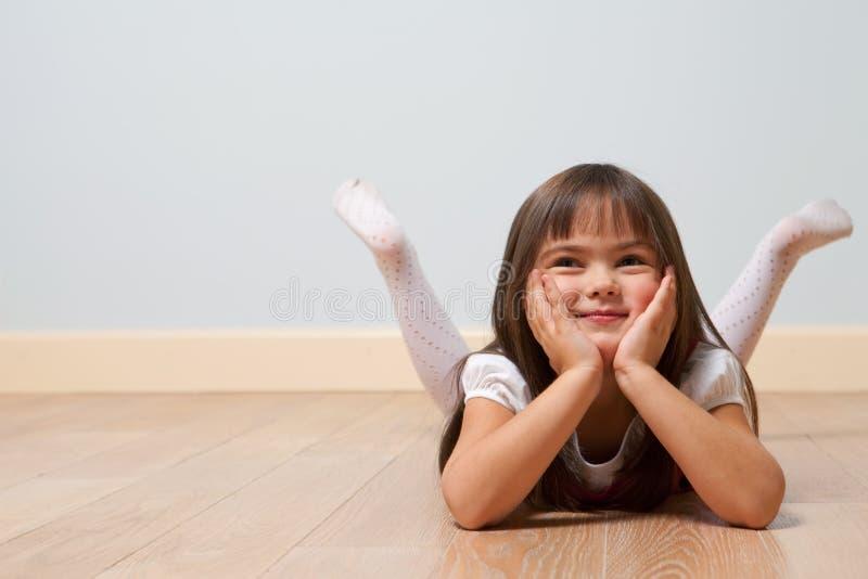 Liegendes nettes Mädchen auf Fußboden stockbilder