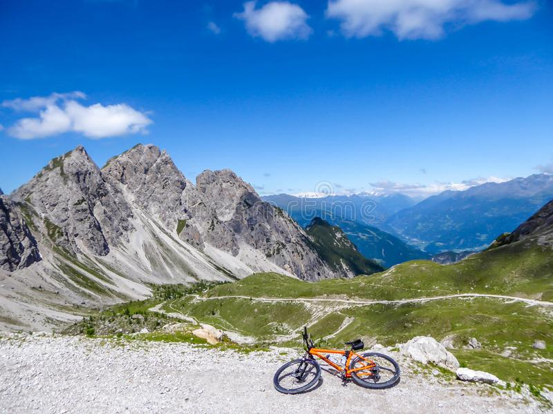 Lienz Dolomites - Mountain bike lying on the side of a gravelled road in tall mountains. Mountain bike lying on the side of a gravelled road in tall mountain royalty free stock image
