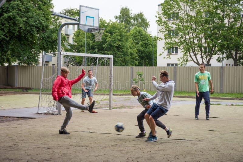 LIEPAJA, LETLAND - JULI 25, 2016: Gelukkige tienerjaren die voetbal o spelen stock fotografie