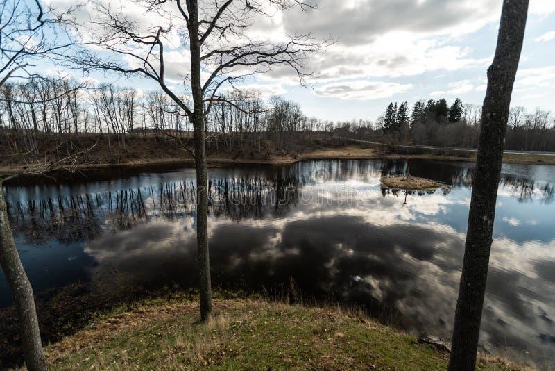 LIEPUPE, LETÓNIA - 13 DE ABRIL DE 2019: Solar de Liepupes Muiza no tempo ensolarado bonito da mola com céu azul e nuvens - lago imagens de stock royalty free