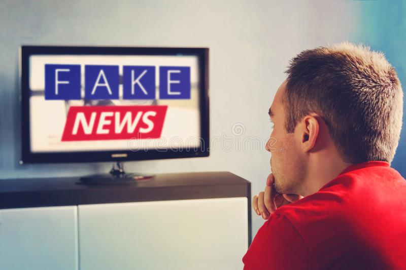 Lies of tv propaganda mainstream media disinformation, A fake news report. viewer is watching TV and doesn`t believe in fake news stock photography