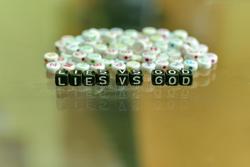 LIES VS GOD  written with Acrylic Black cube with white Alphabet Beads on the Glass Background. LIES VS GOD written with Acrylic Black cube with white Alphabet stock photography