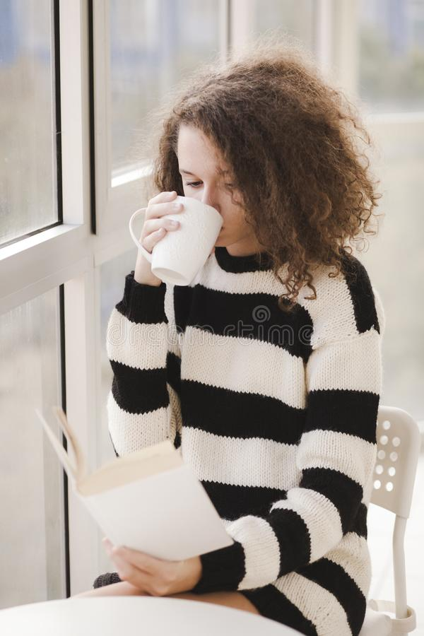 Liest jugendlich Tee driks Mädchen des gelockten Haares und Buch zu Hause stockfoto