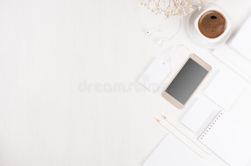 Lieu de travail élégant moderne avec la papeterie blanche vide, l'espace de copie, téléphone, café, fleurs sur le conseil en bois images libres de droits