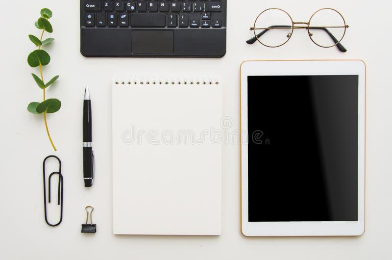 Lieu de travail étendu plat Table blanche de bureau avec l'ordinateur portable, les agrafes, les verres, le carnet et le stylo Vu image libre de droits