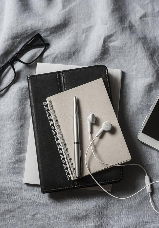 Lieu de travail avec des affaires, accessoires d'éducation Tablette, téléphone, écouteurs, bloc-notes, stylo, verres sur le fond  photographie stock