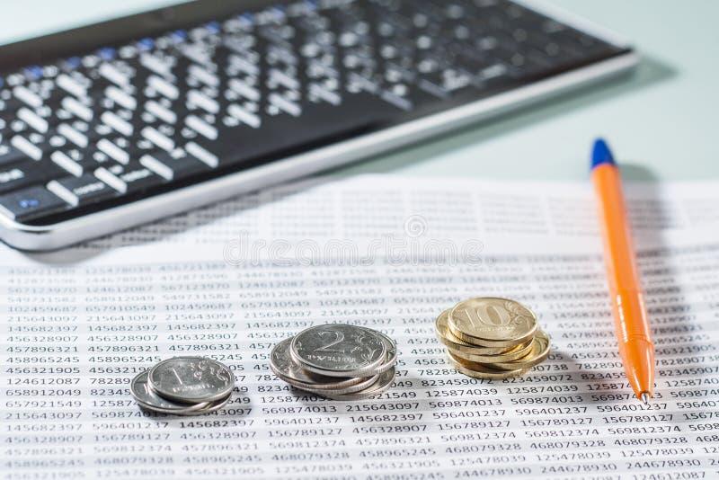 Lieu de travail avec des pièces de monnaie, des documents, le clavier et le stylo images stock