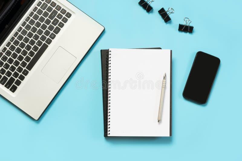 Lieu de travail avec l'accessoire d'ordinateur portable, blanc et noir ouvert sur la table bleue L'espace de vue supérieure et de image stock