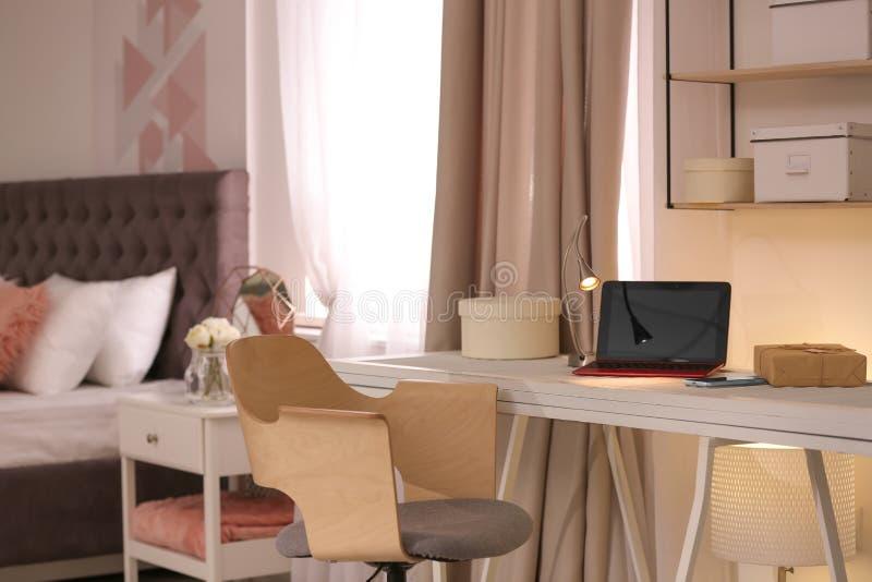 Lieu de travail avec l'ordinateur portable et lit en appartement élégant photo libre de droits