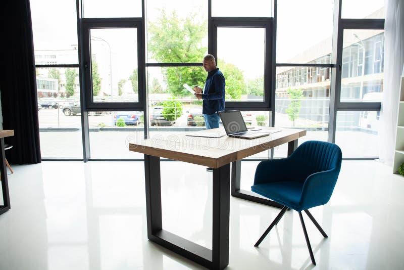 Lieu de travail avec la table de travail confortable d'ordinateur portable de carnet dans la vue de fenêtres et de ville de burea photos stock