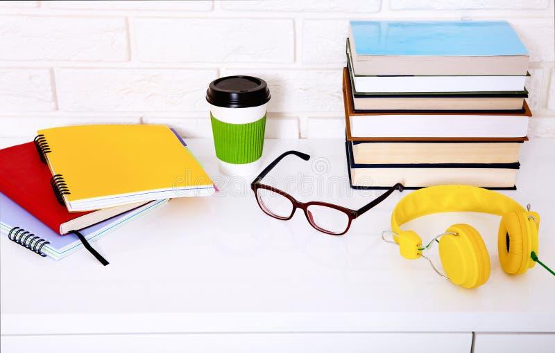Lieu de travail avec la tasse de café et de substance d'éducation dans la chambre Mur de briques et papiers colorés Foyer sélecti images stock
