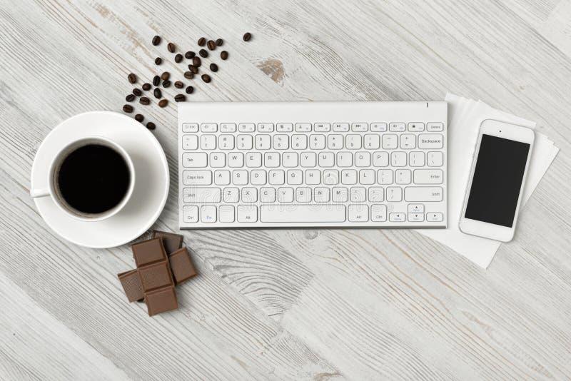 Lieu de travail avec la tasse de café, de clavier, de smartphone et de chocolat sur la surface en bois dans la vue supérieure image stock
