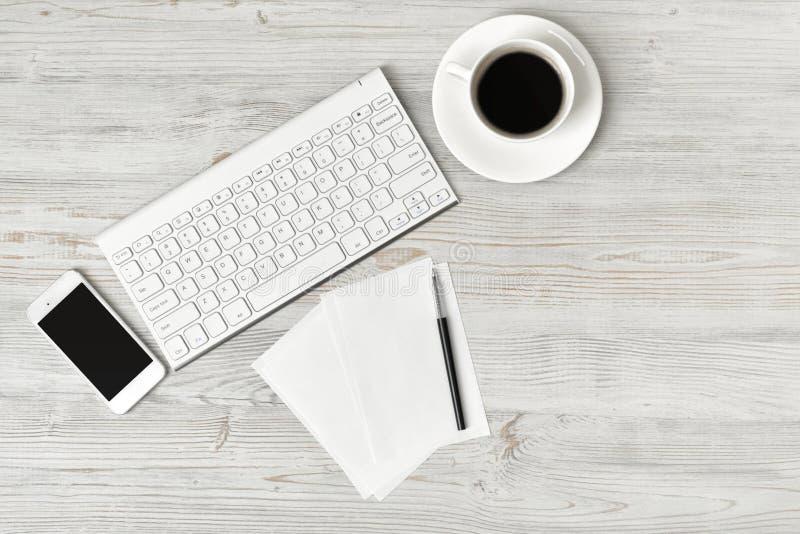 Lieu de travail avec la tasse du café, du clavier, du smarthphone, des feuilles blanches et du stylo sur la surface en bois dans  photos stock