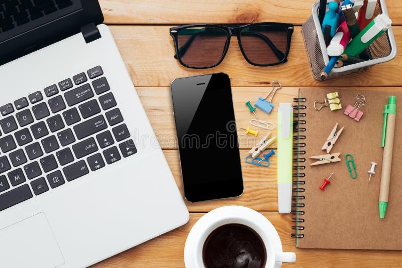 Lieu de travail avec le téléphone et le carnet de café d'ordinateur portable sur la table en bois photographie stock