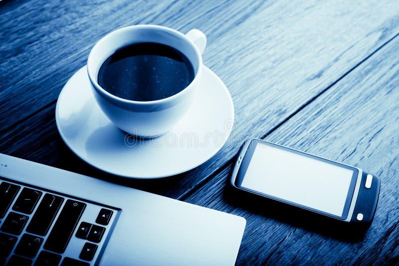 Lieu de travail de bureau avec l'ordinateur portable ouvert sur le bureau en bois avec le téléphone et photos libres de droits