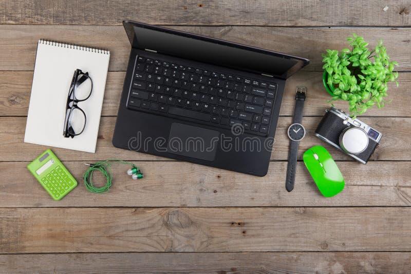 Lieu de travail de ci-dessus - ordinateur portable, bloc-notes, verres et caméra sur le bureau en bois photos stock