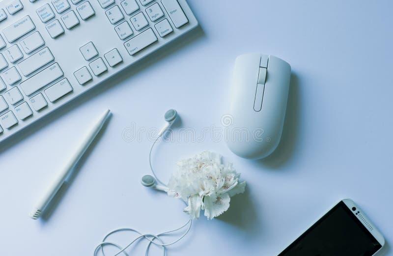 Lieu de travail - clavier, souris d'ordinateur, produit chimique, casque, téléphone blanc images stock