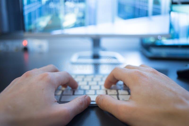 Lieu de travail d'un indépendant : Mains de dactylographie, écran à l'arrière-plan trouble photo stock