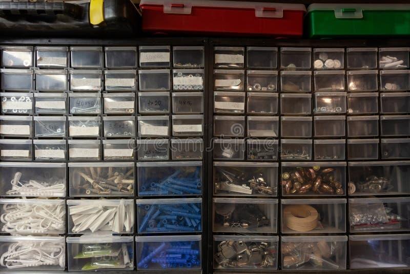 Lieu de travail dans l'atelier : boîtes pour de petites choses avec des vis, des écrous et des doigts photographie stock libre de droits